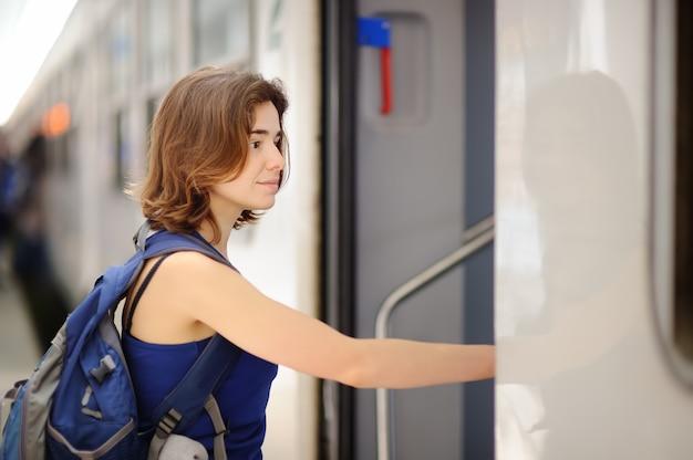 Молодая женщина с рюкзаком сесть на поезд.