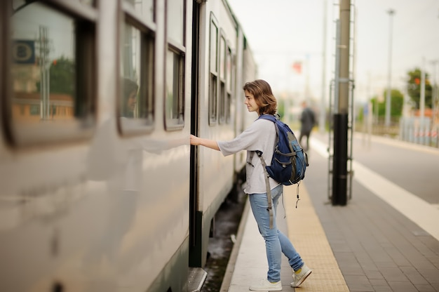 Young woman with backpack take the train.
