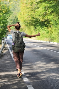 Young woman with backpack tries to stop passing car to hitchhike