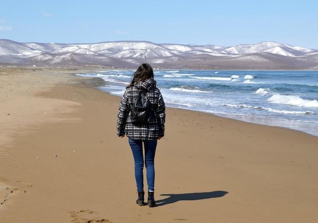 雪山と日本海に近いビーチを歩くバックパックを持つ若い女性