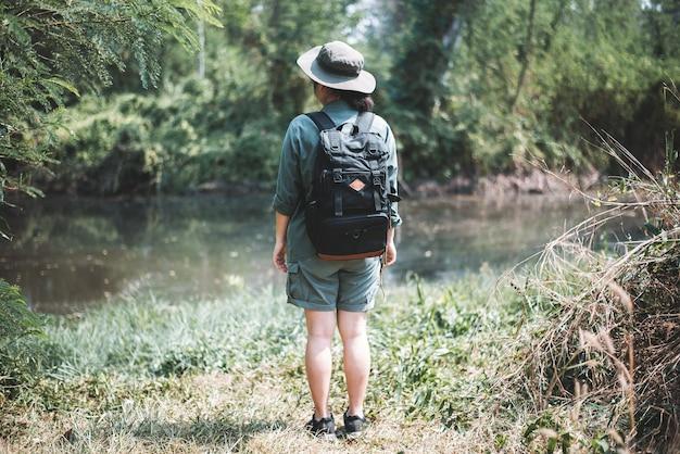 열대 휴가 개념 숲과 호수에서 배낭 야생 모험을 가진 젊은 여자
