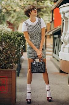 通りの外でバッグを持つ若い女性