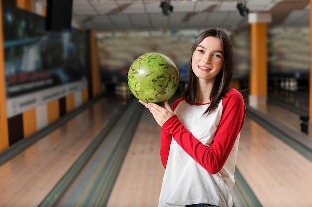 Молодая женщина с мячом в боулинг-клубе