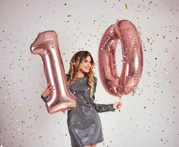 Молодая женщина с воздушными шарами в форме 10