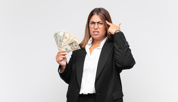 Young woman with banknotes feeling confused and puzzled, showing you are insane, crazy or out of your mind