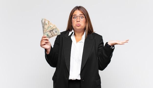 지폐가 의아해하고 혼란스럽고 의심스럽고 가중하거나 다른 옵션을 선택하는 젊은 여성