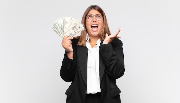 Молодая женщина с банкнотами выглядит отчаянной и разочарованной, напряженной, несчастной и раздраженной, кричит и кричит