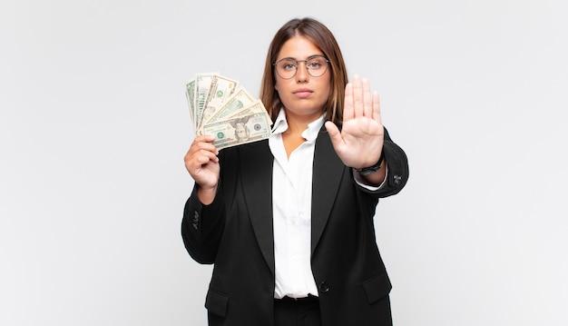 Молодая женщина с банкнотами выглядит серьезной, суровой, недовольной и сердитой, показывая открытую ладонь, делая жест стоп
