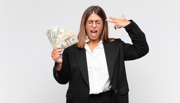 不幸でストレスの多い紙幣を持った若い女性、手で銃のサインを作る自殺ジェスチャー、頭を指して