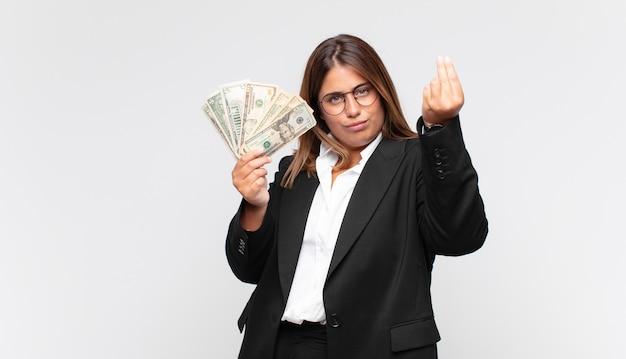 紙幣を持った若い女性が、借金を返済するように言って、お金のジェスチャーをします。
