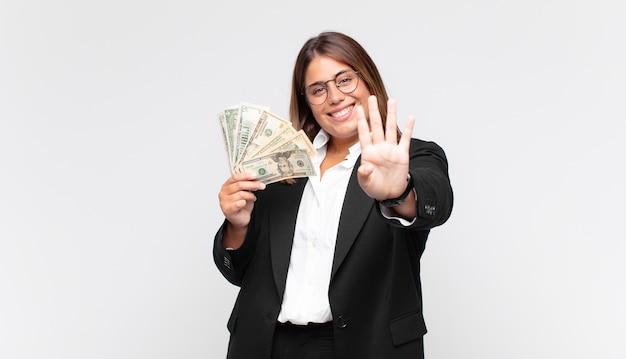 Молодая женщина с банкнотами улыбается и выглядит дружелюбно, показывает номер четыре или четвертый с рукой вперед, отсчитывая
