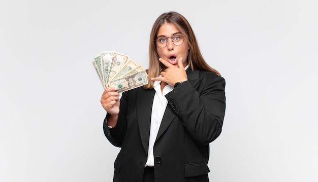 Молодая женщина с банкнотами с широко открытыми глазами и рукой на подбородке
