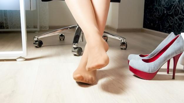 Молодая женщина с босой ногой под офисным столом.