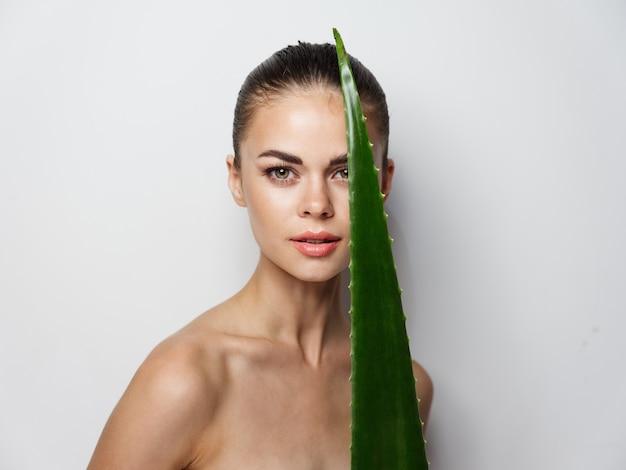 彼女の顔とトリミングされたビューの前に緑のアロエの葉を保持している裸の肩を持つ若い女性