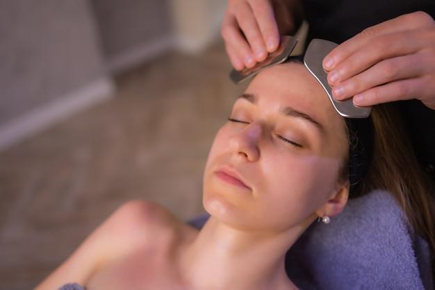 Молодая женщина с голыми плечами, используя массажер для лица, стоя изолированной на коричневом фоне и глядя в сторону.