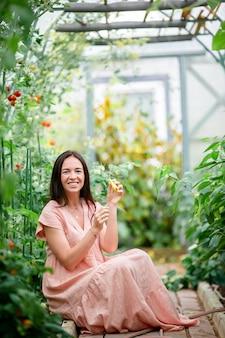 Молодая женщина с корзиной зелени и овощей в теплице. время сбора урожая