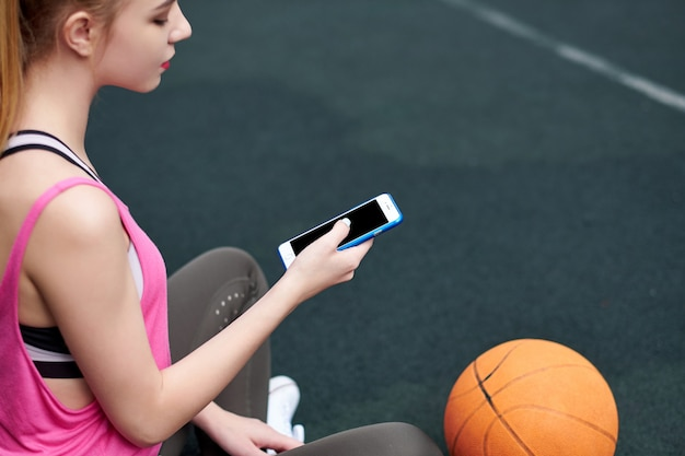 Young woman with basketball using phone after training. black screen
