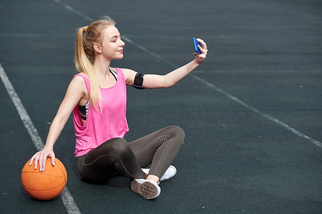 Young woman with basketball using phone after training, making selfie