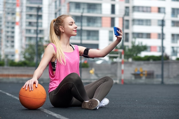 トレーニング後に電話を使って、自撮りをするバスケットボールを持つ若い女性。