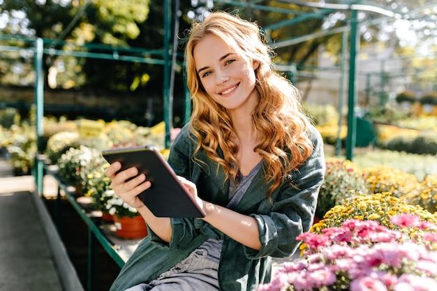 美しいブロンドの髪と優しい笑顔の若い女性は、ベルト付きの緑のローブを着て温室で働いています