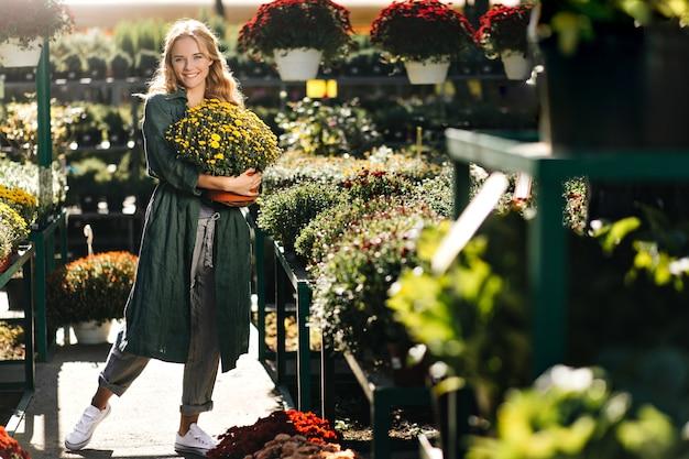 Молодая женщина с красивыми светлыми волосами и нежной улыбкой, одетая в зеленый халат с поясом, работает в теплице