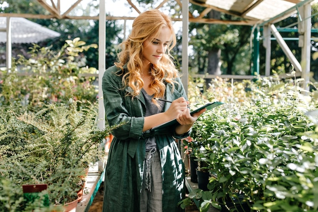 Young woman with beautiful blond hair and gentle smile, dressed in green robe with belt is working in greenhouse