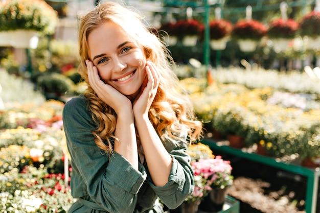 Giovane donna con bei capelli biondi e un sorriso gentile, vestita di una tunica verde con cintura sta lavorando in serra