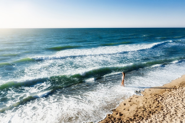 夕暮れ時のビーチに立って遠くを見つめる美しい体の若い女性。ポジティブな気分、夏休み、日当たりの良いコンセプト
