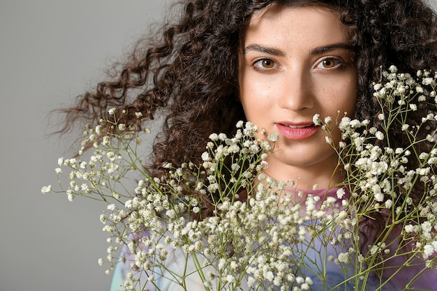 Young woman with beautiful curly hair and flowers on grey background