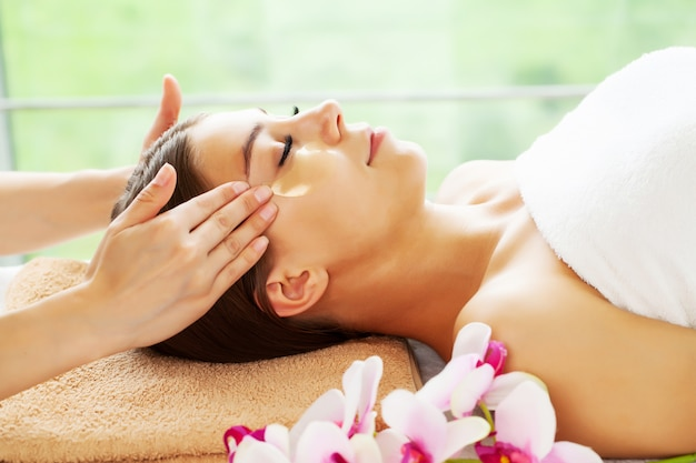 Young woman with beautiful face on facial massage in beauty studio