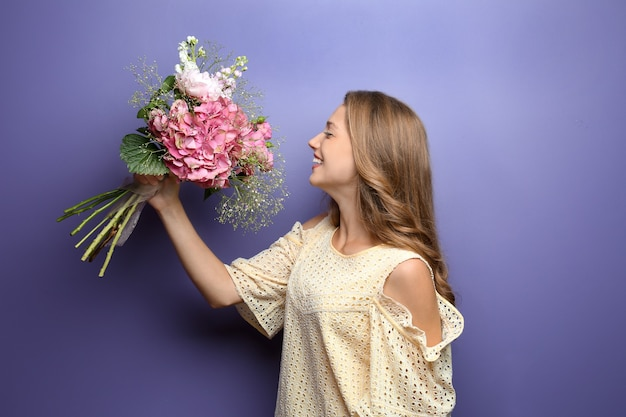 色の表面に美しい花を持つ若い女性