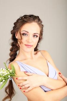 灰色の背景に美しい髪型と花を持つ若い女性