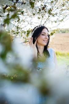 공원의 푸른 잎사귀 배경에 꽃다발을 얹은 푸른빛 드레스를 입은 빈티지 후프와 아름다운 화장을 한 젊은 여성. 흰색 꽃과 신선한 초상화 매력적인 소녀입니다.
