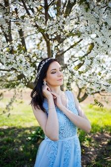 Молодая женщина с красивым макияжем с винтажным обручем в голубом легком платье с букетом позирует на фоне зеленой листвы в парке. свежий портрет привлекательной девушки с белыми цветами.