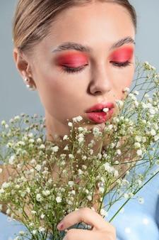 灰色の背景に美しい化粧と花を持つ若い女性