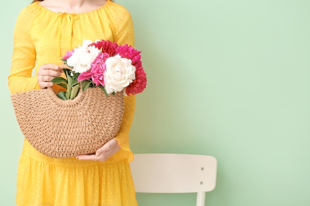 Молодая женщина с красивыми цветами пиона в сумке на цветном фоне
