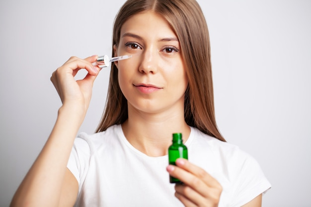Young woman with beautiful skin puts vitamins on her face