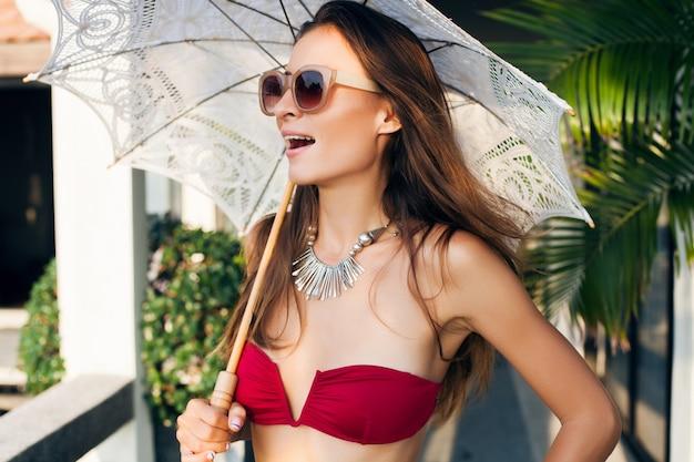アジアの休暇旅行中にトロピカルヴィラリゾートでレースの太陽傘を保持している赤いビキニ水着を着ている美しいスリムな体を持つ若い女性、細い体型、夏のスタイルのトレンドアクセサリー