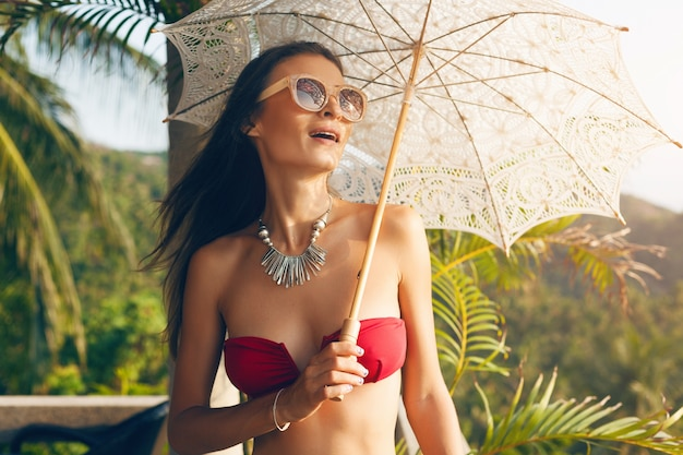 Young woman with beautiful slim body wearing red bikini swimsuit holding lace sun umbrella on tropical villa resort during vacation travel in asia, skinny figure, summer style trend accessories