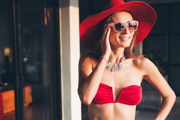Giovane donna con un bel corpo snello che indossa costume da bagno bikini rosso, cappello di paglia e occhiali da sole che si distendono sul resort villa tropicale durante le vacanze in asia, figura magra, accessori di tendenza in stile estivo
