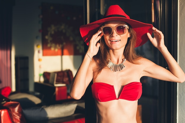 Young woman with beautiful slim body wearing red bikini swimsuit, straw hat and sunglasses relaxing on tropical villa resort during vacation in asia, skinny figure, summer style trend accessories