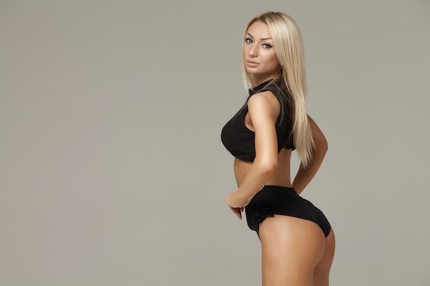스튜디오에서 포즈 아름 다운 슬림 건강 한 몸매를 가진 젊은 여자. 회색 배경에 운동복 피트니스 여성 모델