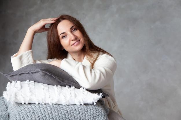 暖かいベージュのローブで美しい笑顔を持つ若い女性は、異なるテクスチャの折り畳まれたベッドシーツのスタックに寄りかかっています。天然コットンとオーガニックコットンの寝具。スペースをコピーします。製造。ホテル業界。