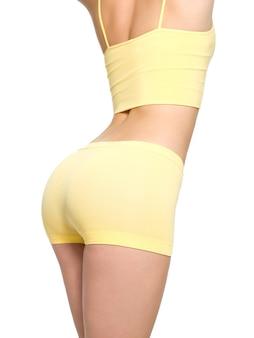 美しいスポーティなお尻とスリムなウエストライン-白で隔離される若い女性