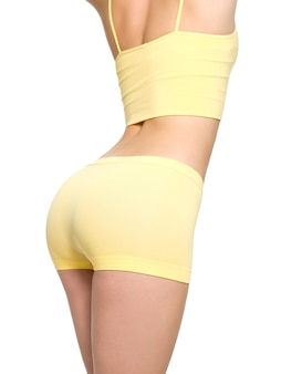 Young woman with beautiful sporty buttocks and slim waistline - isolated on white