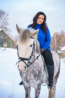 A young woman with a beautiful winter white horse
