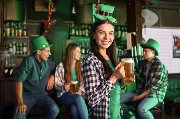 パブで聖パトリックの日を祝うビールと若い女性