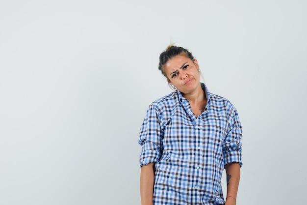 市松模様のシャツで首を曲げて悲しそうに見える若い女性。