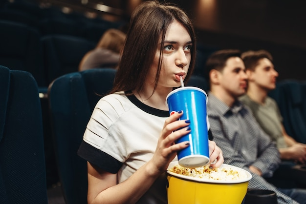 Young woman with beverage and popcorn sitting in cinema. showtime, movie watching