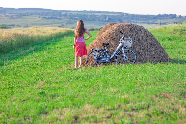 Young woman with a bicycle on field with haystacks on a sunny day